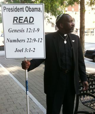 Rev. Dennis Stiles with sign
